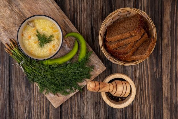 まな板の上のディルと木製の背景に黒胡椒とライ麦パンのスライスのバスケットとボウルと唐辛子のチキンオルゾスープの上面図 無料写真
