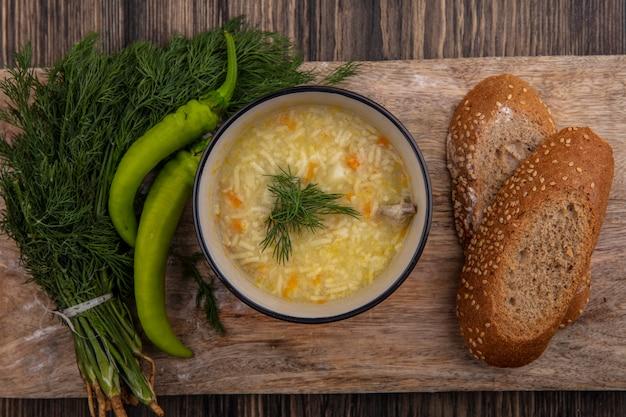 ボウルに鶏肉のオルゾスープと木製の背景のまな板にディルとコショウと種をまく茶色の穂軸パンスライスの上面図 無料写真