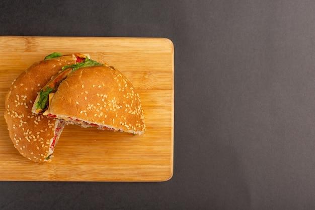 Вид сверху куриного сэндвича с зеленым салатом и овощами внутри, нарезанными половинками на деревянной поверхности Бесплатные Фотографии