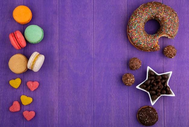 Вид сверху шоколадного пончика с мармеладными шоколадными конфетами и макаронами на ярко-фиолетовой поверхности Бесплатные Фотографии