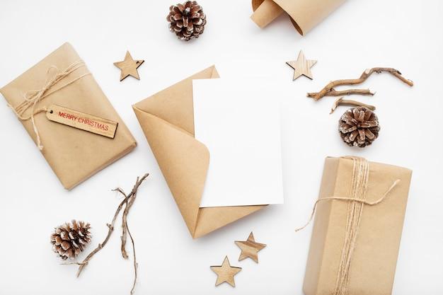 ギフトボックス、リボン、モミの枝、コーン、白いテーブルの上のアニスとクリスマスの構成の上面図 無料写真