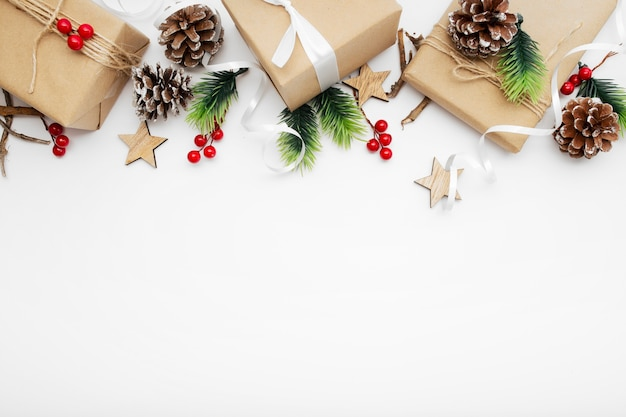 선물 상자, 리본, 전나무 가지, 콘, 흰색 테이블에 아니스와 크리스마스 구성의 상위 뷰 무료 사진