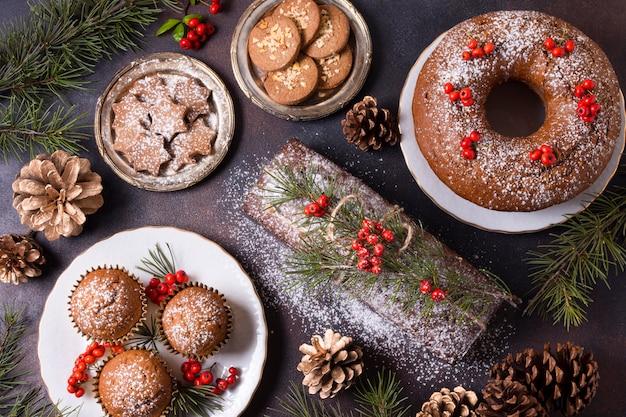 Вид сверху рождественских десертов с красными ягодами и сосновыми шишками Premium Фотографии