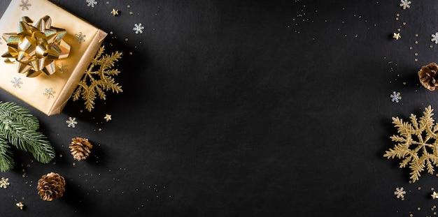 Вид сверху рождественской подарочной коробки, еловых веток, сосновых шишек и снежинки Premium Фотографии