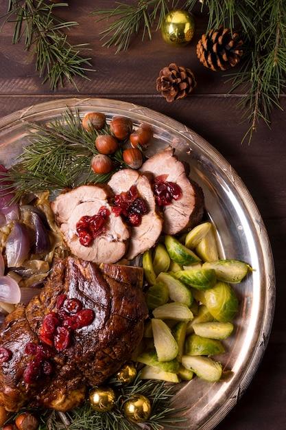 Вид сверху рождественского стейка на тарелке с декором из сосновых шишек Бесплатные Фотографии