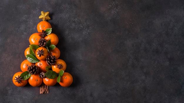 Вид сверху формы елки из мандаринов и сосновых шишек с копией пространства Premium Фотографии