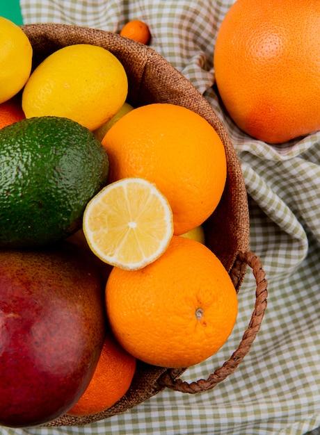 格子縞の布の背景にバスケットにマンゴーオレンジアボカドレモンとして柑橘系の果物のトップビュー 無料写真