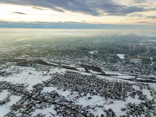 Вид сверху пригородов города или красивых домов небольшого городка на зимнее утро на фоне облачного неба. концепция фотографии с помощью дронов. Premium Фотографии
