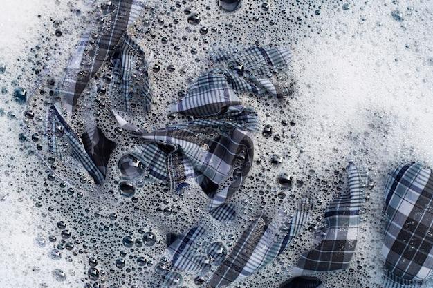 服の平面図は、粉末洗剤の水の溶解に浸します。ランドリーのコンセプト Premium写真