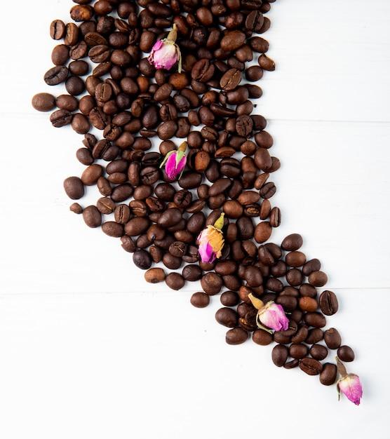 Вид сверху кофейных зерен и чайной розы бутоны разбросаны на белом фоне Бесплатные Фотографии