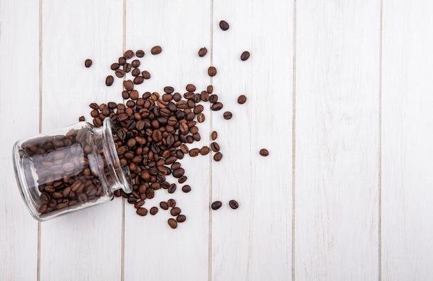 コピースペースと白い木製の背景の上のガラス瓶から落ちるコーヒー豆の上面図 無料写真