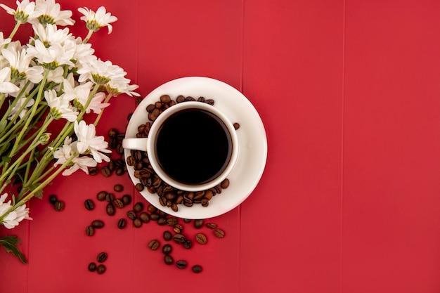 コピースペースと赤い背景に花と白いカップのコーヒーの上面図 無料写真