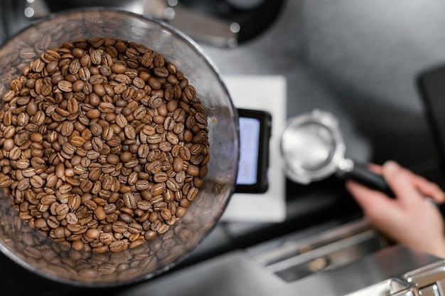Вид сверху жареных зерен кофе и женщина-бариста, готовящая кофе Бесплатные Фотографии