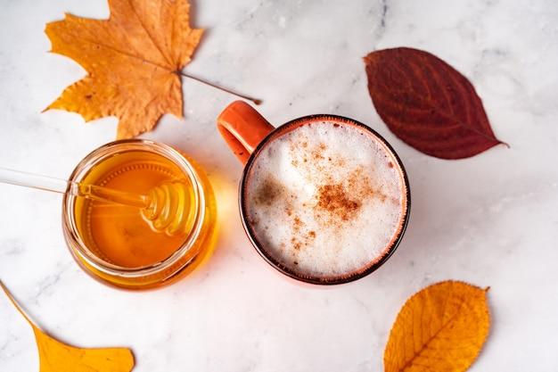 白い大理石の表面にミルクの泡とシナモン、蜂蜜の瓶、オレンジ色の紅葉とコーヒーのトップビュー Premium写真