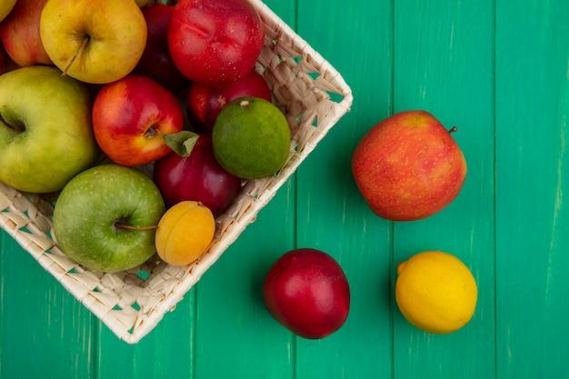 緑の表面に桃レモンとライムのバスケットに着色されたリンゴのトップビュー 無料写真