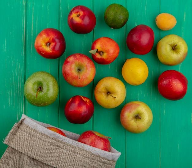 緑の表面に黄麻布の袋に桃レモンとライムと着色されたリンゴのトップビュー 無料写真