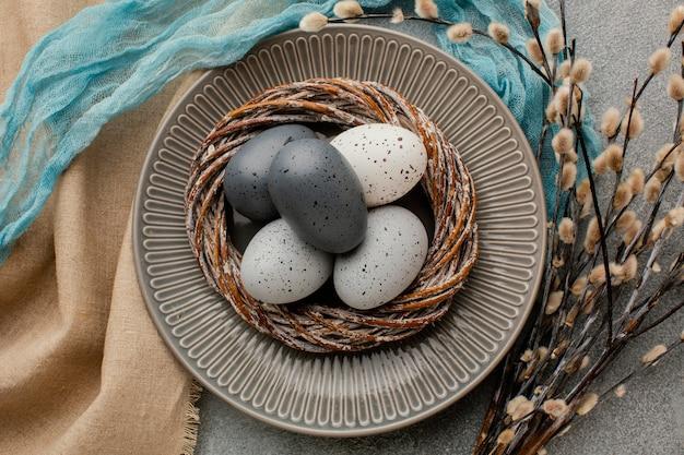 꽃과 함께 접시에 바구니에 착 색된 부활절 달걀의 상위 뷰 무료 사진
