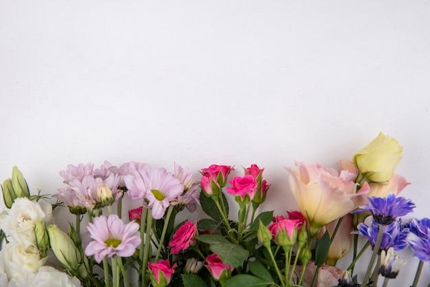 スペースと白い背景の上のバラやデイジーの花などのカラフルで素晴らしい花の上面図 無料写真