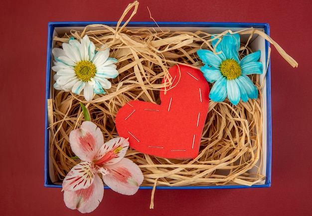 カラフルなデイジーの花とピンクのアルストロメリアの上面と赤い色の紙から作られた心と赤いテーブルの青いプレゼントボックスにストロー 無料写真