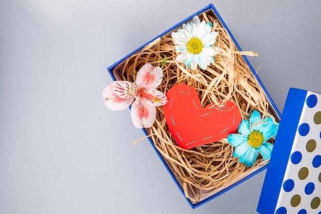 カラフルなデイジーの花とピンクのアルストロメリアの赤い色の紙から作られた心とコピースペースを持つ白いテーブルの青いプレゼントボックスにストローのトップビュー 無料写真