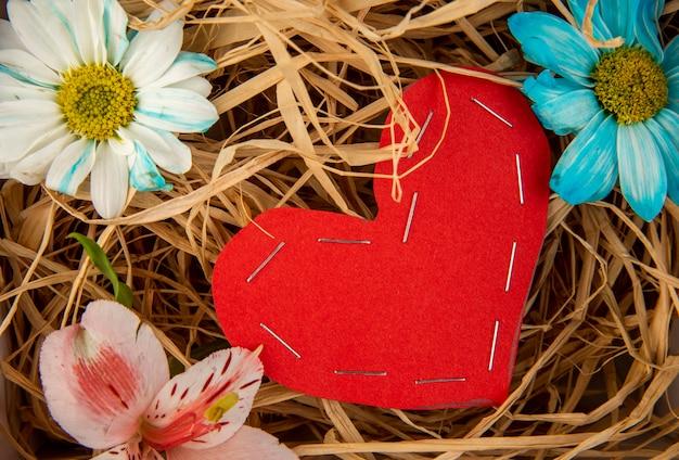 カラフルなデイジーの花とわらのテーブルに赤い色の紙から作られた心とピンクのアルストロメリアのトップビュー 無料写真