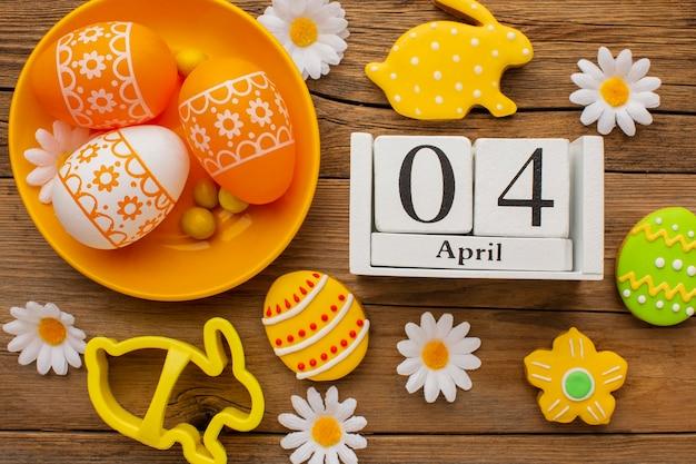 카모마일 꽃과 날짜와 함께 접시에 다채로운 부활절 달걀의 상위 뷰 무료 사진