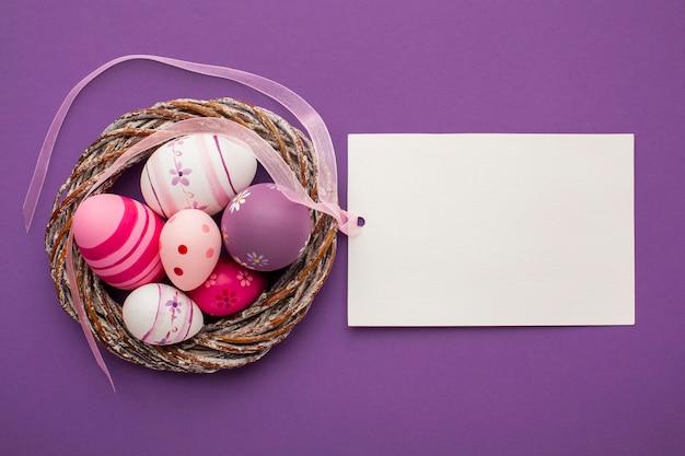 Вид сверху красочные пасхальные яйца с корзиной и бумагой Бесплатные Фотографии