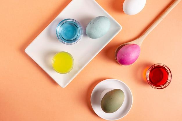 Вид сверху красочных расписных пасхальных яиц с краской Premium Фотографии