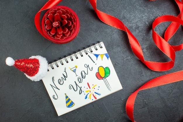 暗い背景に新年の書き込みとサンタクロースの帽子と赤いリボンとノートブックと針葉樹の円錐形の上面図 無料写真