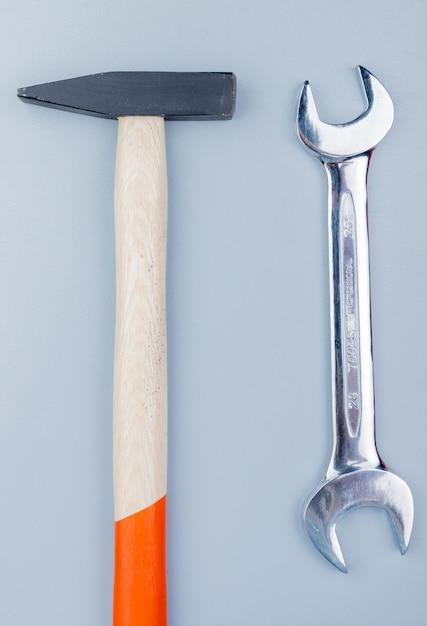 Вид сверху строительных инструментов в виде кирпичного молотка и гаечного ключа на сером фоне Бесплатные Фотографии