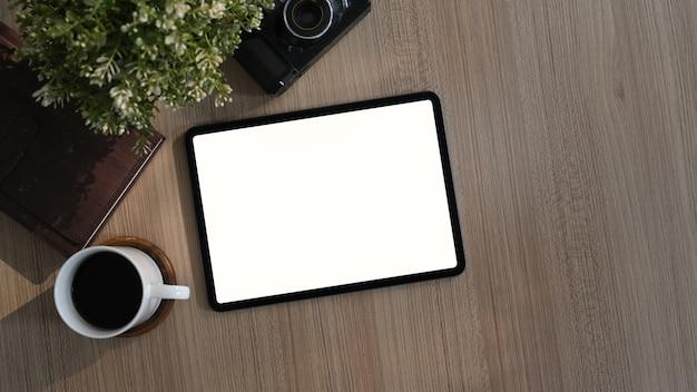 Взгляд сверху современного рабочего места с кофейной чашкой, заводом, книгой и таблеткой на деревянном столе. пустой экран для монтажа продукта. Premium Фотографии