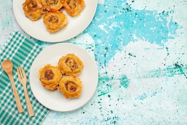 Вид сверху приготовленной муки из теста с мясным фаршем внутри тарелок на ярко-синем столе, калорийность мяса из теста Бесплатные Фотографии
