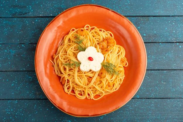 Вид сверху приготовленной итальянской пасты, вкусной еды с зеленью внутри оранжевой тарелки на синей деревянной деревенской поверхности Бесплатные Фотографии