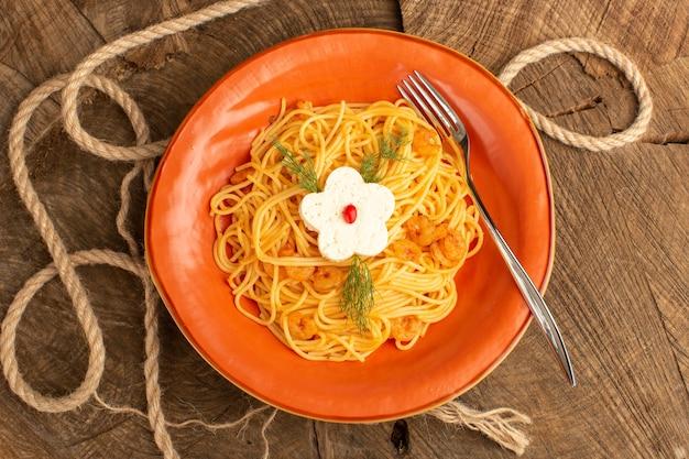 Вид сверху приготовленной итальянской пасты с зеленью внутри оранжевой тарелки на деревянном столе Бесплатные Фотографии