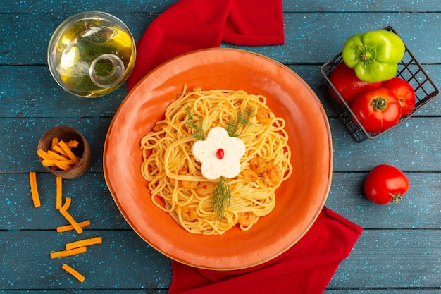 Вид сверху приготовленной итальянской пасты с зеленью внутри оранжевой тарелки с маслом и овощами на синей деревянной поверхности Бесплатные Фотографии