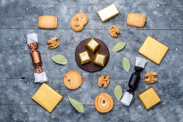 Вид сверху печенья и грецких орехов вместе с шоколадным тортом на сером, шоколадном сладком печенье Бесплатные Фотографии