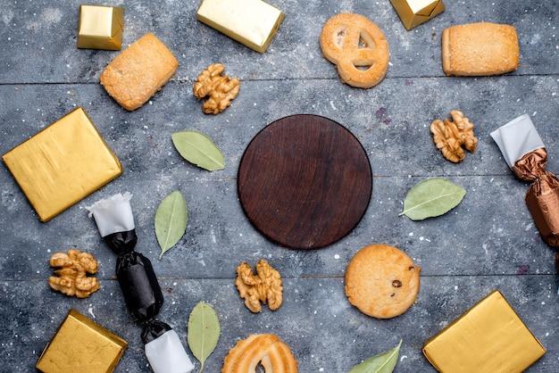 Вид сверху на печенье и грецкие орехи вместе с шоколадным пирогом на сером, печенье, печенье, шоколад Бесплатные Фотографии