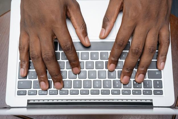 노트북 키보드에 입력 카피라이터 손의 상위 뷰. 집에서 프리랜서 프로젝트를 일하는 남자, 정보 검색 프리미엄 사진