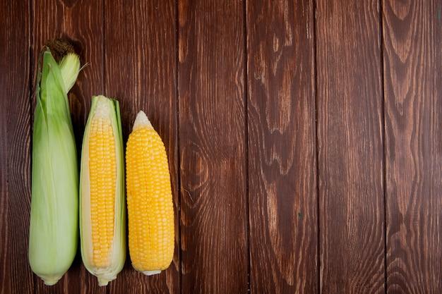左側のシェルとトウモロコシの穂軸とコピースペースと木材のトップビュー 無料写真