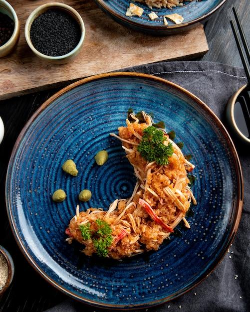 皿に野菜とわさびと黒の醤油とカニのサラダのトップビュー 無料写真