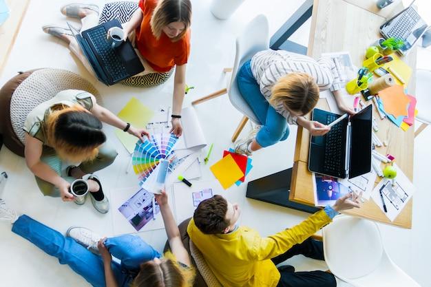 オフィススペースで非公式の会合を持つ創造的な労働者の平面図です。カラーサンプル、部屋のレイアウト、ラップトップ、消耗品を使用して床で作業する建築家およびインテリアデザイナー。チームワークの概念。 Premium写真