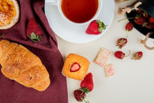 三日月形の平面図は、布の上にカリカリのクリスプブレッドとイチゴとお茶のカップと白い表面にホワイトチョコレートとカップケーキ 無料写真