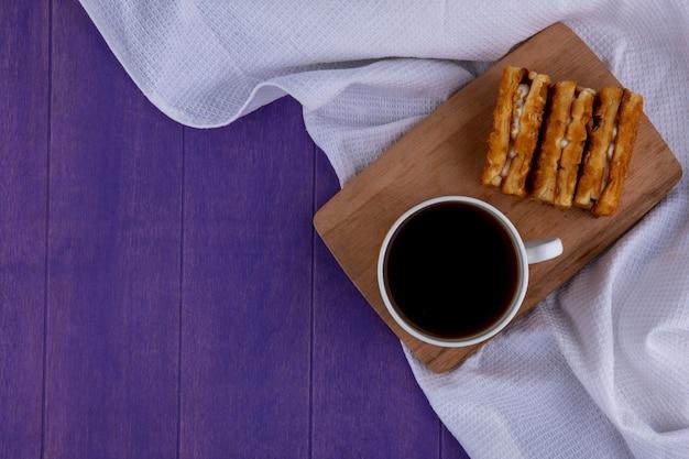白い布と紫色の背景にまな板の上のコーヒーとケーキのトップビュー 無料写真