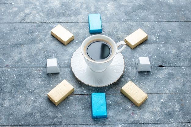 熱くて強い一杯のコーヒーの上面図、水色の机の上に金で形成されたチョコレートの裏地、コーヒーココアドリンクホット 無料写真