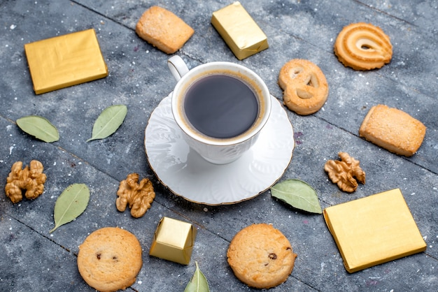 Вид сверху чашки кофе с грецкими орехами печенья на сером столе, сладкое печенье печенье Бесплатные Фотографии