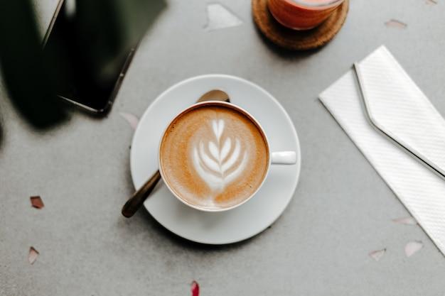 거품과 크림, 냅킨에 플라스틱 빨대와 대리석 조명 테이블에 전화가있는 커피 한잔의 상위 뷰 무료 사진