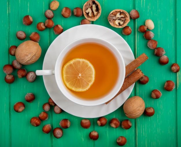 緑の背景にナッツとクルミのパターンの受け皿にレモンとシナモンを入れたホットトディのカップのトップビュー 無料写真