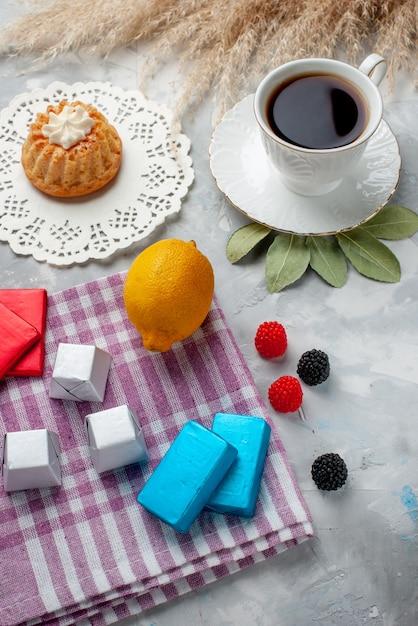 ライトデスク上のケーキレモンチョコレート、ティーチョコレートキャンディーケーキと白いカップの中で熱いお茶のカップの上面図 無料写真