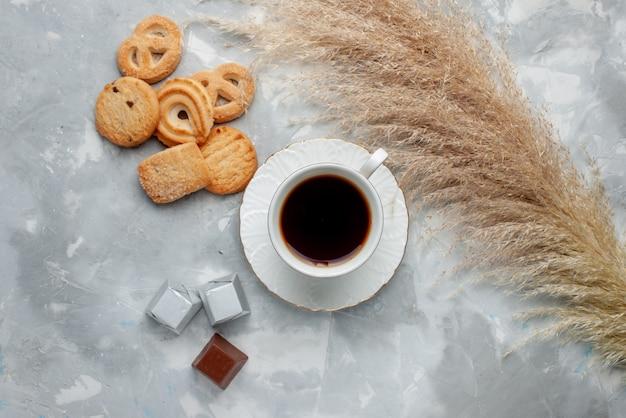 光の上のチョコレートとクッキー、クッキーキャンディーチョコレートティークッキーと熱いお茶の上面図 無料写真