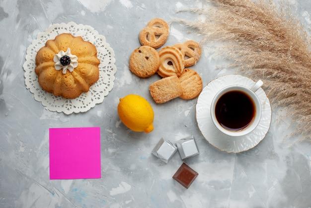 Вид сверху на чашку горячего чая с шоколадом, лимоном и печеньем на светлом полу, печенье, конфеты, шоколад, чай, печенье, сладкое Бесплатные Фотографии